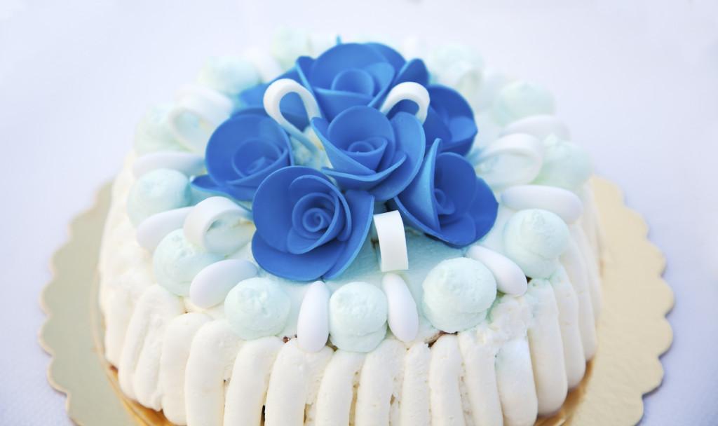 raffinata e delicata la torta bianca con panna e fiori in pasta di zucchero blu acceso