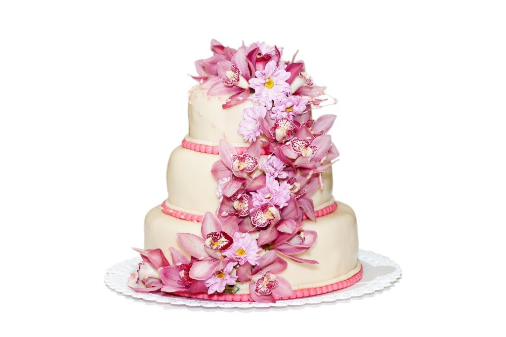 una torta bianca romanticissima , con una fascia di fiori rosa e indaco ripiena di crema pasticcera e fragoline di bosco