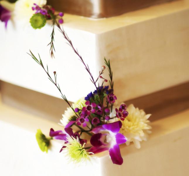 Dettaglio floreale sulla torta quadrata con nastri a contrasto.