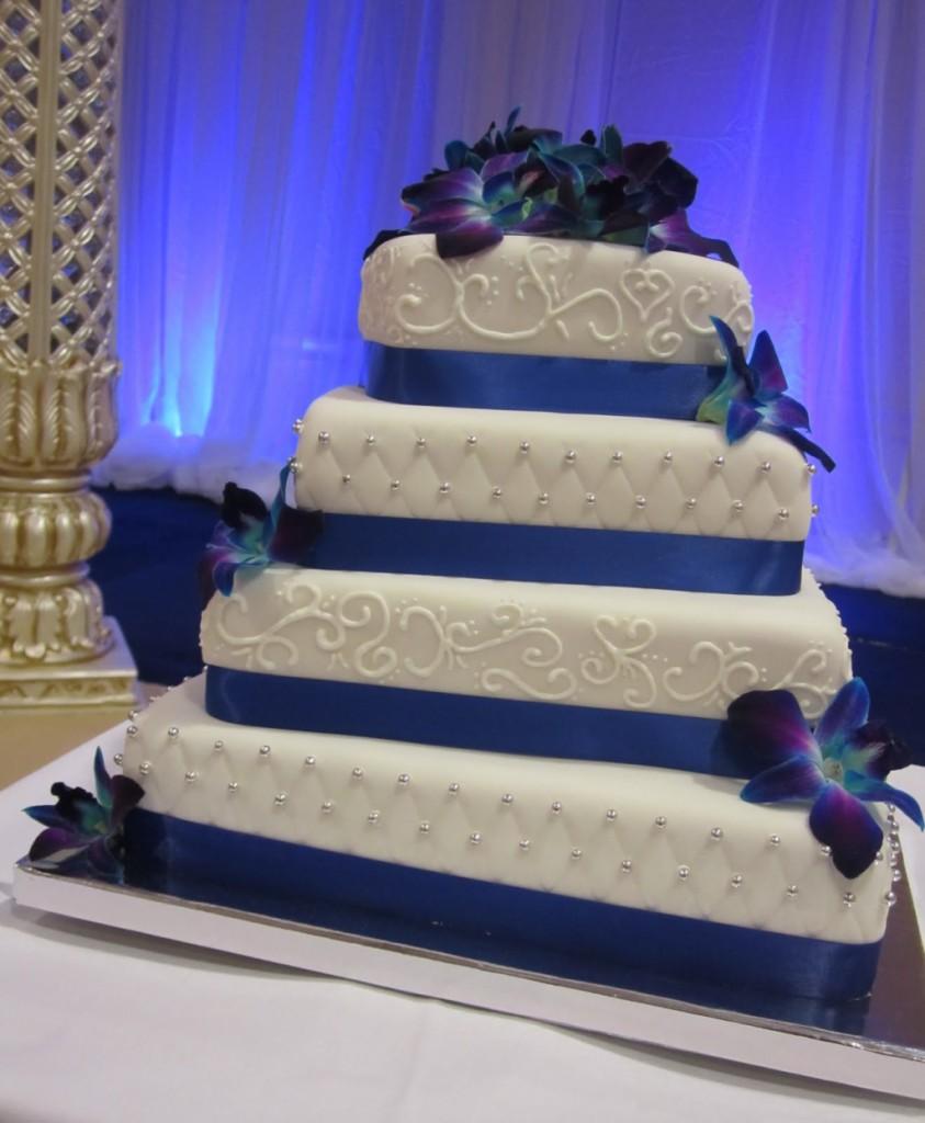 torta nuziale a piani con orchidee blu e nastro della stessa tonalità foto by cakechooser