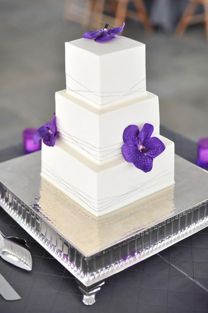 semplice torta nuziale quadrata a piani semplice bianca con orchidee viola
