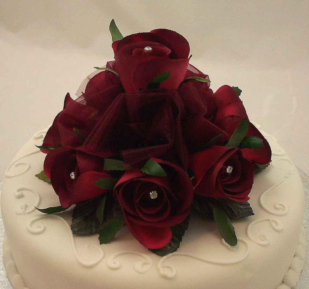 torta nuziale bianca a un piano con bouquet rose rosse e punti luce
