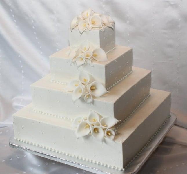 Il massimo della rigorosità e pulizia: torta nuziale a piani quadrati completamente bianca e piccoli decori.