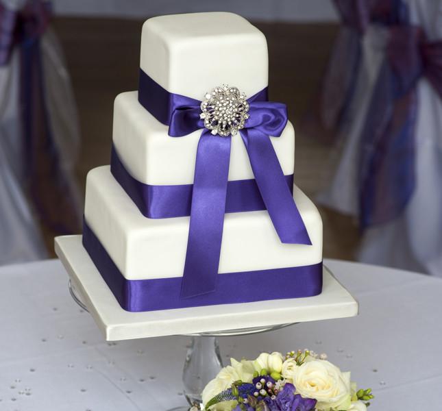 Elegante e chic la torta a piani quadrati con nastri viola e spilla vintage.
