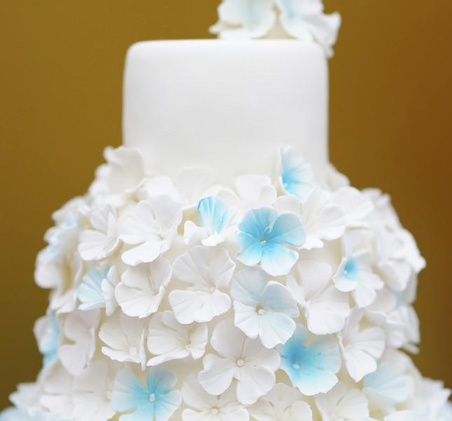 Fiori di zucchero che si posano delicatamente sulla torta bianchissima.