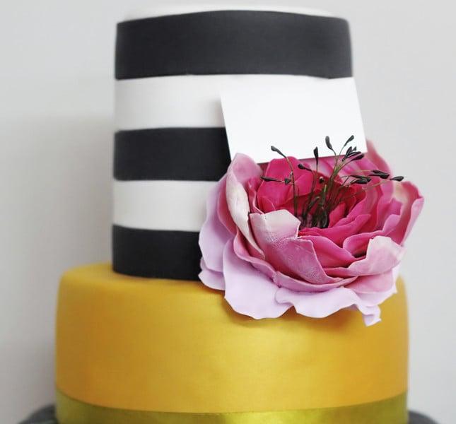Sbarazzina la torta multicolor dal sapore estico: oro, bianco e ner e un grande fiore fuxia.