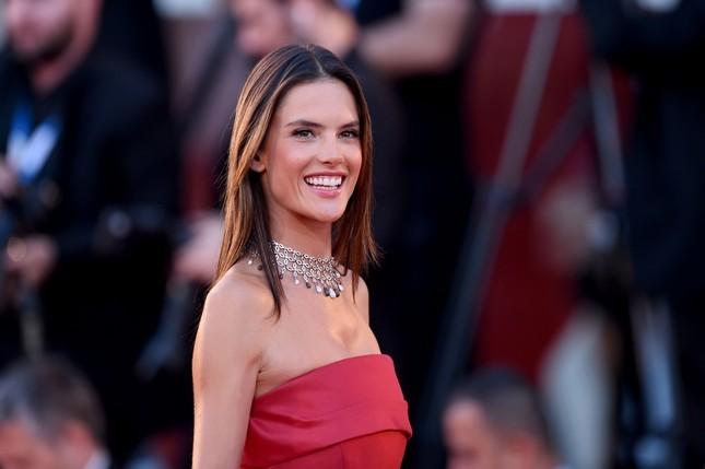 L'angelo di Victoria's Secret Alessandra Ambrosio, sul red carpet della Mostra del Cinema di Venezia 2014, indossa un abito rosso di Alberta Ferretti, impreziosito da una collana di diamanti con pietre bianche e nere.