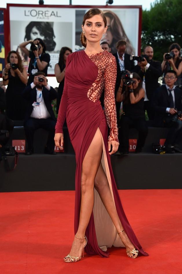 La splendida modella Victoria Bonya, indossa sul red carpet un abito bordeaux asimmetrico con uno spacco pronunciato, di Zuhair Murad e scarpe di Dolce & Gabbana. I capelli vengono raccolti da un elegante chignon laterale