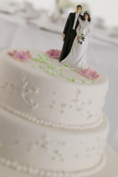Torta ricoperta di pasta di zucchero color rosa chiaro, con roselline pink baby e statuette sposini. La base è rotonda, simboleggiando l'unione e l'armonia