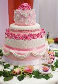 Torta sui toni del rosa decorata con roselline in pasta di zucchero