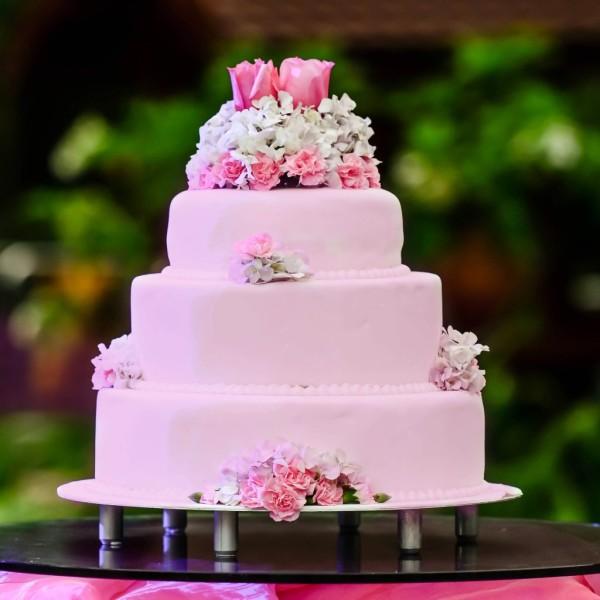 Torta rosa a quattro piani: la scelta della torta a più strati è tornata molto di moda e ricorda ai due sposi il percorso in salita che devono compiere insieme nella vita, la torta è in pasta di zucchero