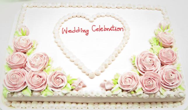 Torta nuziale rosa, classica a un solo piano ma allo stesso tempo originale per vi della base rettangolare. La copertura in panna e le roselline glassate completano il tutto.