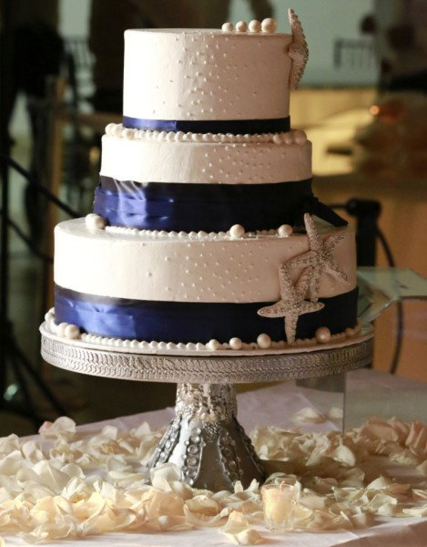 L'accostamento del rosa cipria con i nastri blu e neri è raffinatissimo. Osa sulla tua torta di pasta di zucchero anche un tema marino, con stelle e qualche conchiglia decorativa.