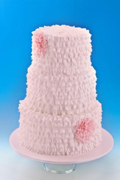 Una proposta molto raffinata, la torta completamente rosa cipria, con decorazioni in panna che ricordano piccole arricciature di tessuto.