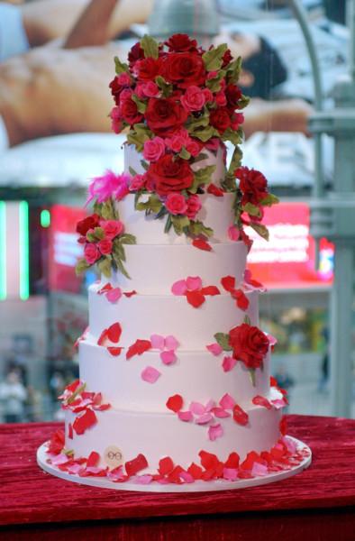 Torta di pasta di zucchero rosa a sette piani con petali rosa e rossi e foglioline verdi. Una soluzione classica e raffinata.