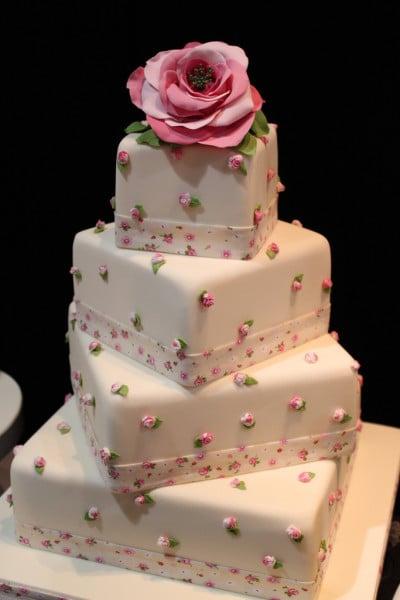 Torta rosa molto tenue, a quattro piani con base quadrata, in pasta di zucchero con roselline e nastrino in pasta di zucchero con fiorellini rosa e verdi