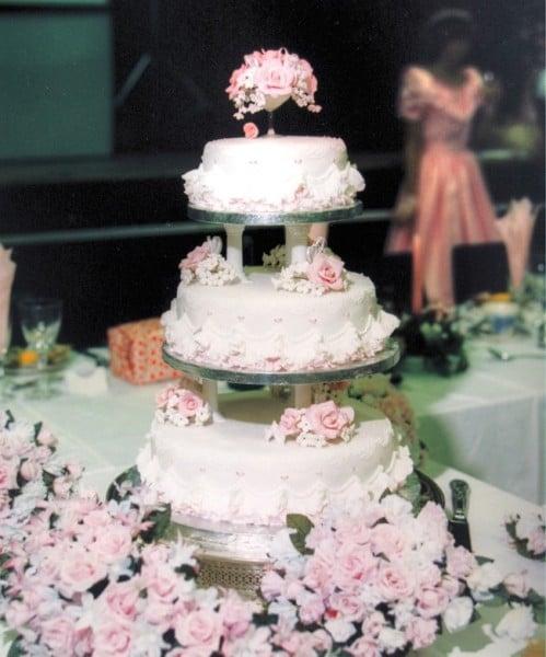 Torta sui toni del rosa tenue, a tre piani, fatta di pasta di zucchero e base ruffle cake. Alcuni fiori la impreziosiscono.