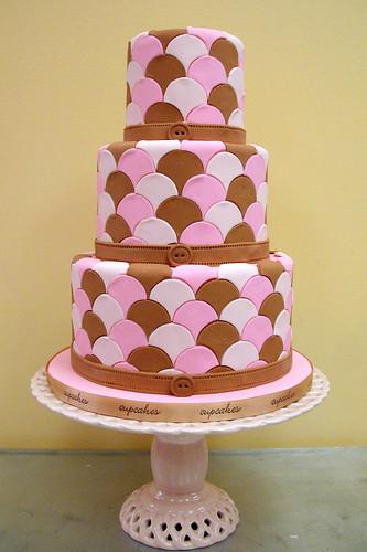 Il rosa e il marrone possono essere abbinati per un'atmosfera vintage che ti stupirà: la torta è a tre piani, in pasta di zucchero, con un mosaico di mezze lune rosa, bianche e marroni.