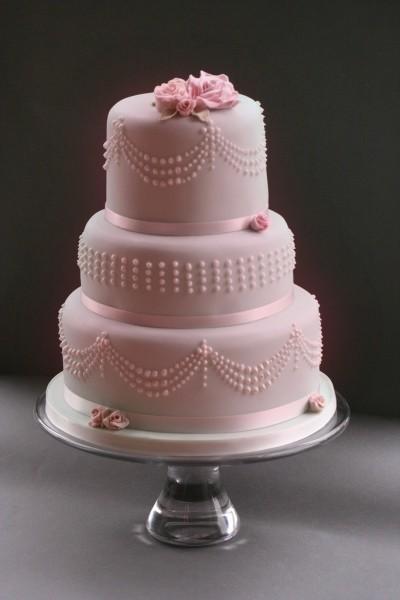 Una scelta classica ma di sicuro successo, è la torta nuziale color rosa tenue, con chiffon cake ricoperta da pasta di zucchero e decorazioni tone sur tone.