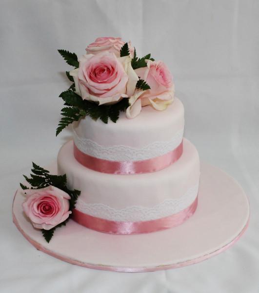 Torta di pasta di zucchero, con base rotonda, a due piani con nastrini e rose tone sur tone, una scelta molto raffinata