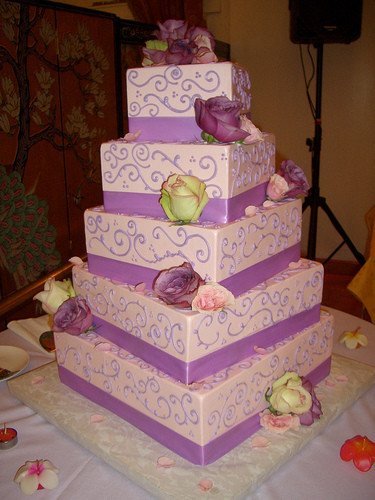 Torta a cinque piani con base quadrata, con interno di chiffon cake ed esterno ricoperto da pasta di zucchero rosa e lilla, nastro lilla abbinato