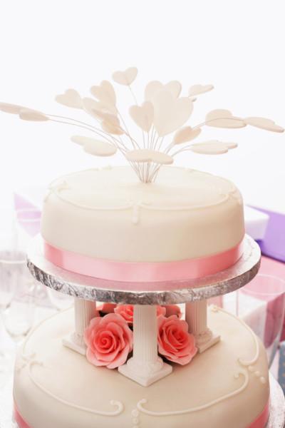 Torta rosa con pasta di zucchero, piedistalli in pasta di zucchero, fiorellini tone sur tone glassati, un particolare della parte superiore con decorazione a cuori