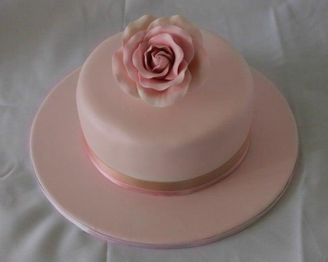 Torta rosa con base unica e fiore in cima, di pasta di zucchero, nastro rosa di raso per un tocco ancora più chic