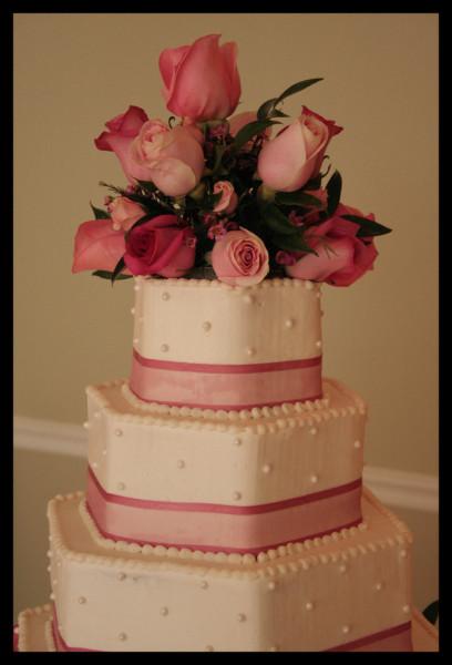 Torta rosa con base esagonale a tre piani, in pasta di zucchero con nastri fucsia e rose come ornamento in cima