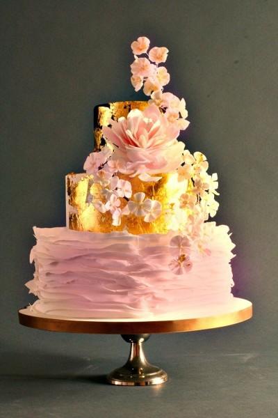 Una torta rosa confetto a tre piani, con base ruffle cake e i due piani successivi avvolti da una copertura dorata: una scelta in stile shabby chic