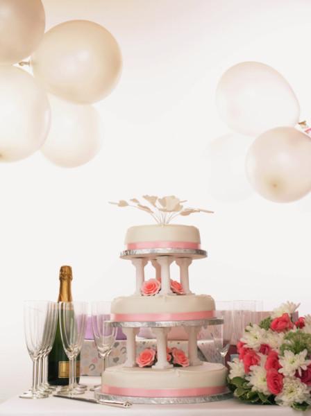 Torta rosa a tre piani in pasta di zucchero su piedistallo, le colonnine sono anch'esse in pasta di zucchero.