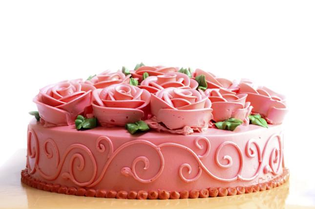 Torta color rosa accesso con rose sopra e foglioline verdi in pasta di zucchero, a un solo piano