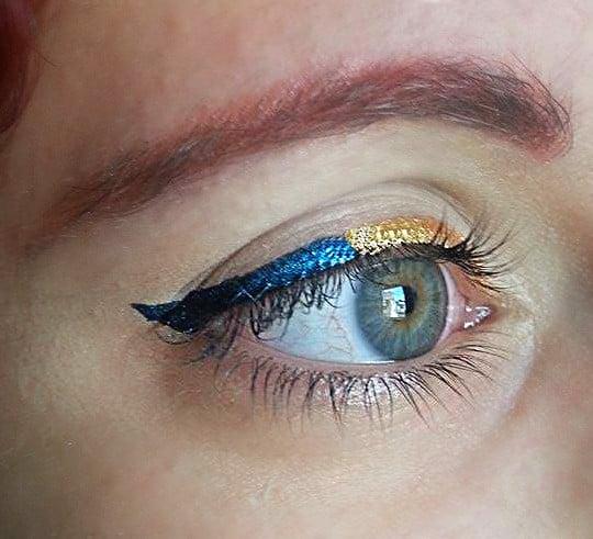 Applicate l'eyeliner blu nella seconda metà dell'occhio, portatelo all'angolo esterno e terminate disegnando la coda
