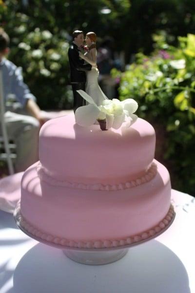 Se desideri che sia tutto perfetto e che la cerimonia rispecchi la tradizione, ma non vuoi rinunciare al colore rosa, opta per questa soluzione a due piani in rosa confetto con i tradizionali sposini appoggiati in cima. La paste è di zucchero.