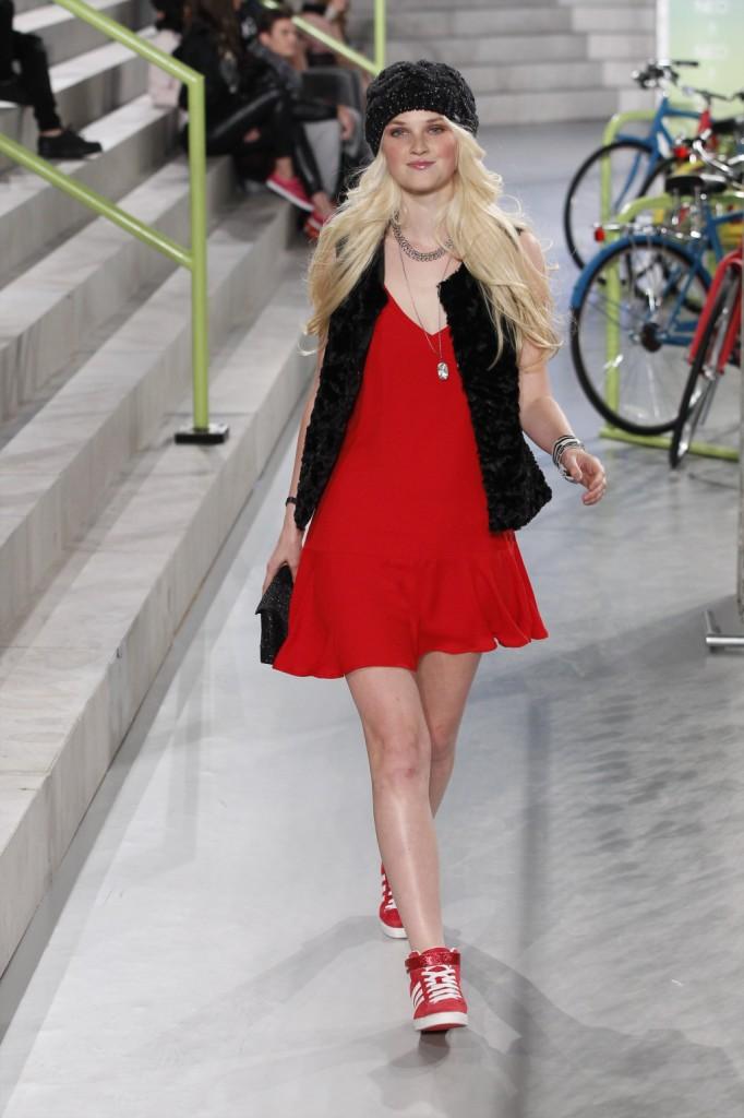 Urban bon ton: il minidress rosso viene sdrammatizzato dal beanie e dalle sneakers