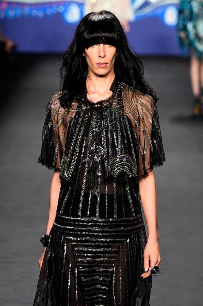 Ispirazione dark per il vestito che gioca su trasparenze e righe argento. Per l'hairstyle, frangia lunga e piena / Anna Sui ss 2015