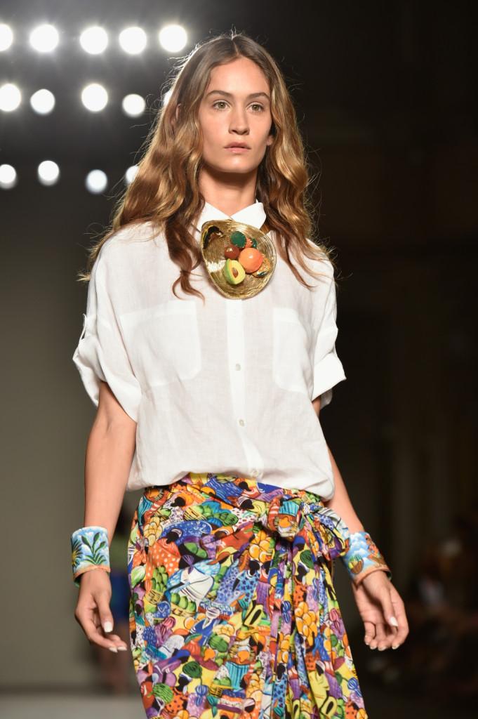 La camicetta bianca coloniale si abbina alla gonna sarong fantasia e a una collana di frutta / Stella Jean ss 2015