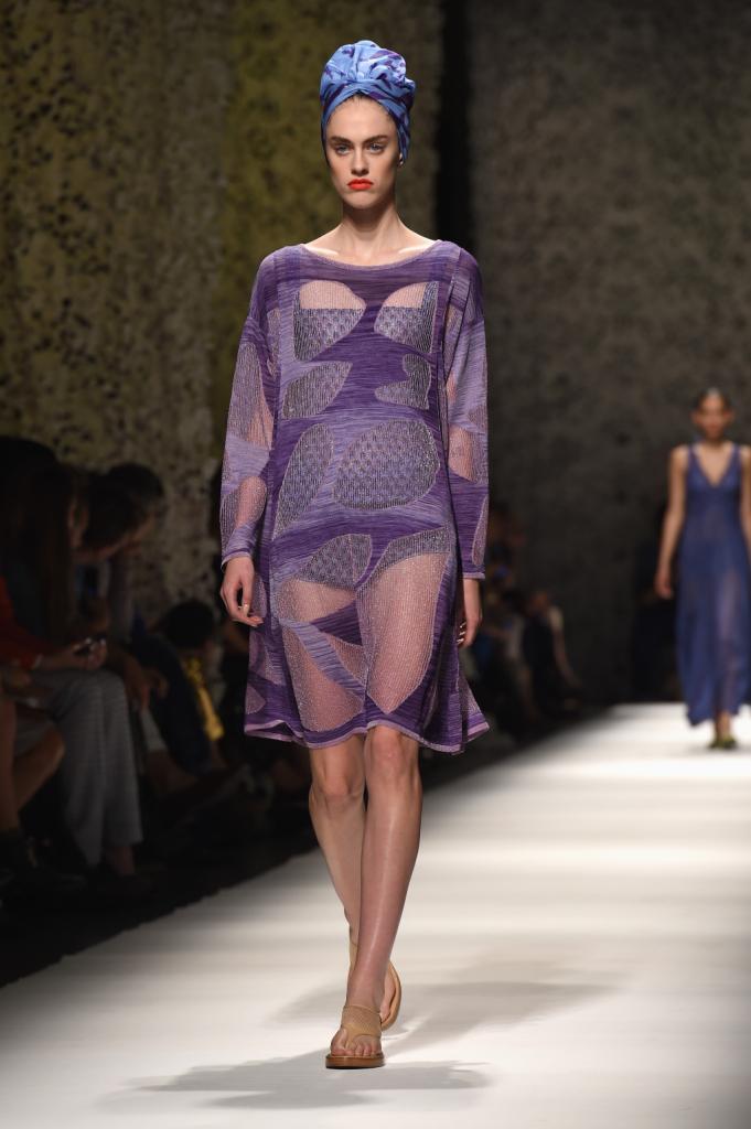 Modella con turbante e abito dal tessuto leggero color viola e mauve