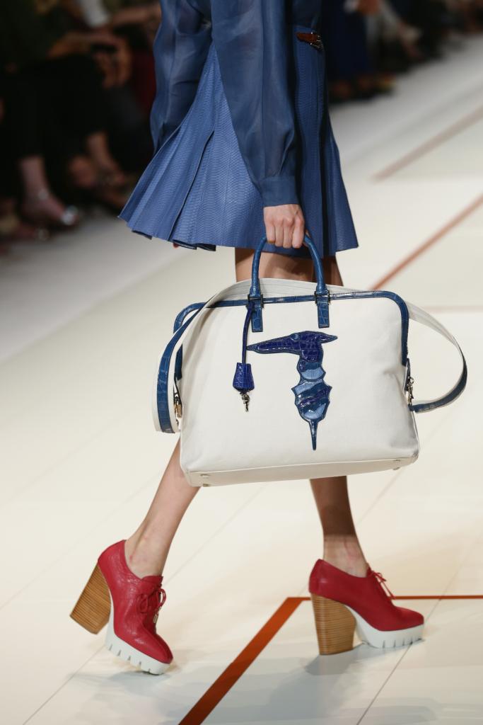 Gli accessori sono i grandi protagonisti della sfilata, come le scarpe: dei sandali colorati con tacco in legno e suola bianca