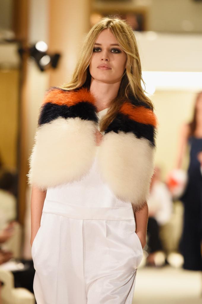 Outfit bianco con pelliccia banca con bande orizzontali nere e arancione