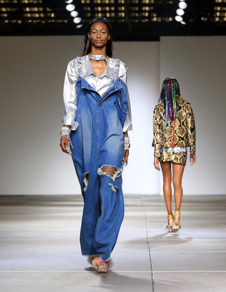 Ashish, LFW, Primavera-estate 2015: salopette in jeans oversize, con apertura a cerniera sul davanti, strappi alle ginocchia e spalline impreziosite da pietre e gemme. Camicia con bavero del collo sul davanti in glitter argentati.
