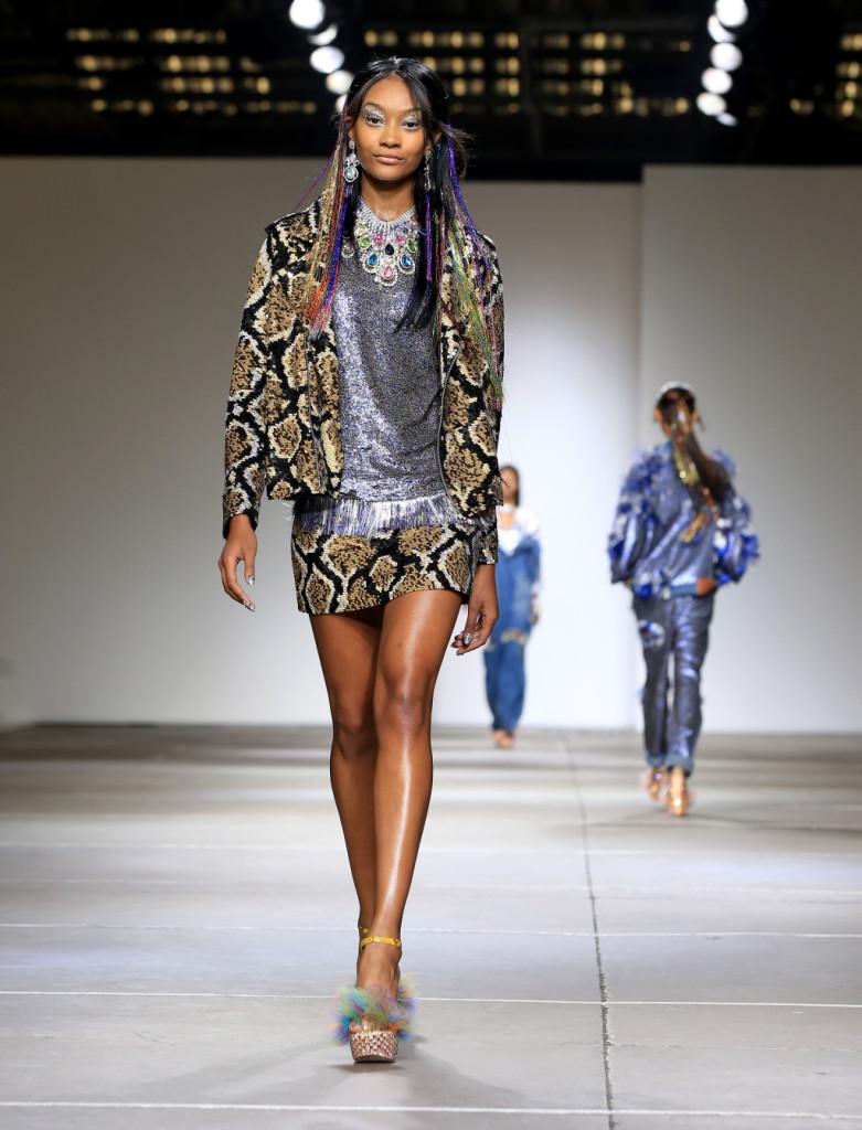 Ashish, LFW, Primavera-estate 2015: minigonna e giacca con cerniera con stampa animalier composta da paillettes  marroni e nere. Maglia glitterata d'argento sotto. Platform con piume e lustrini