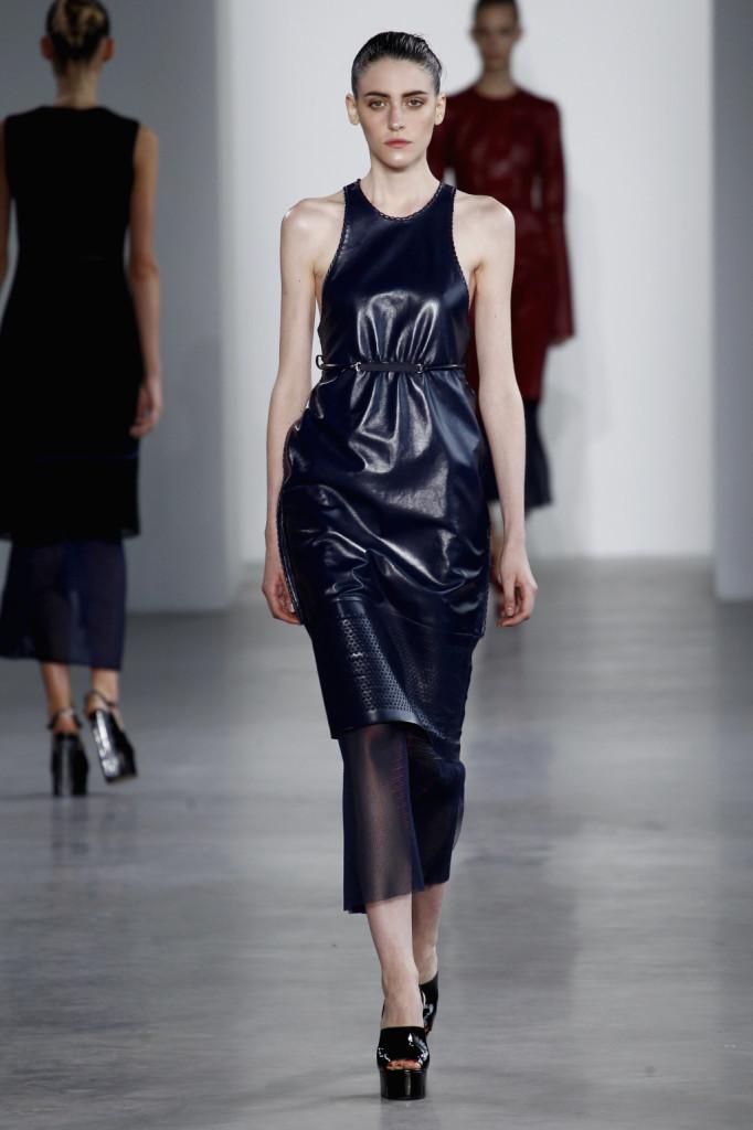 Calvin Klein, NYFW, Primavera-estate 2015: vestito-canotta blu navy in pelle verniciata traforata e gonna in viscosa velata. La canotta è con il dorso in vogatore ultra-ampio