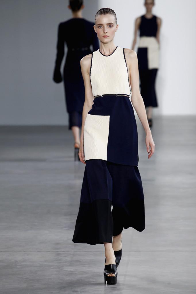 Calvin Klein, NYFW, Primavera-estate 2015: vestito-canotta con dorso a vogatore ultra ampio, top e gonna plissettati bon ton sovrapposti a pantalone scampanato con pannelli neri e blu