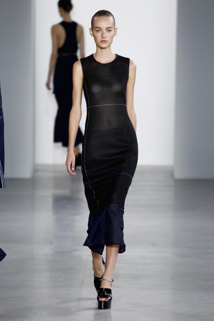 Calvin Klein, NYFW, Primavera-estate 2015: canotta-vestito con trama a rete nera e girocollo anteriore, longuette blu in viscosa velata che spunta da sotto l'abito