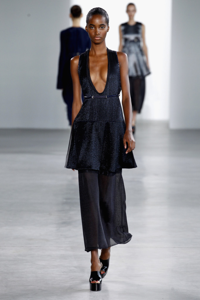Calvin Klein, NYFW, Primavera-estate 2015: miniabito con ampia scollatura sul davanti, trama in filo d'argento a squama di pesce, sovrapposto a longuette velata