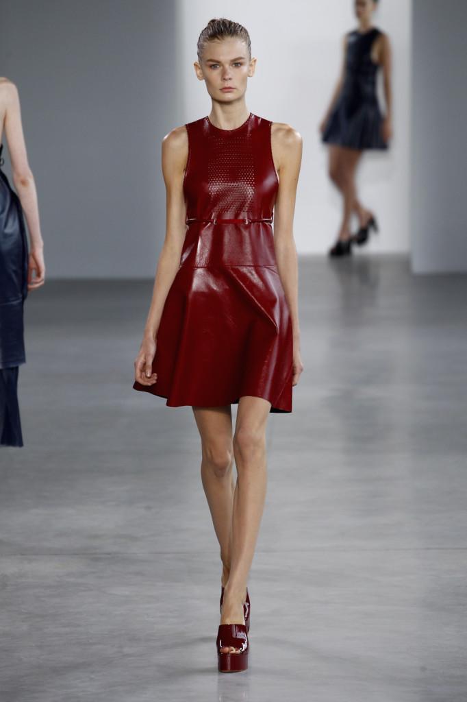 Calvin Klein, NYFW, Primavera-estate 2015: miniabito in pelle rosso smalto, canotta con dorso a vogatore e pannello traforato sul petto. Cinturina e platform color rosso smalto e gonna a ruota.