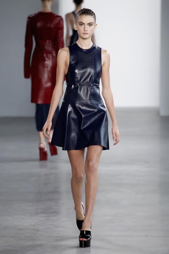 Calvin Klein, NYFW, Primavera-estate 2015: miniabito blu navy in pelle laccata con pannello traforato sul petto e cinturina taglio impero