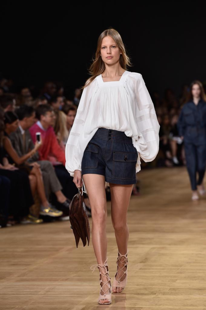 Chloè, PFW, collezione Primavera-Estate 2015: blusa bianca in stile rinascimentale con maniche ampie e drappeggi, shorts in denim con bottoni e tasche ampie
