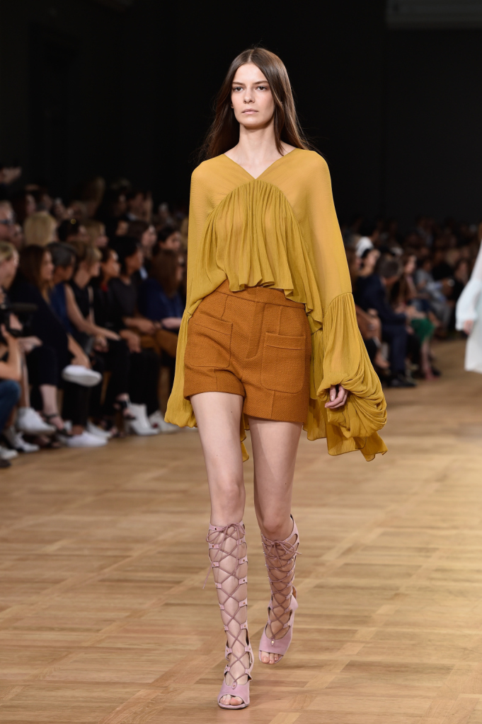 Chloè, PFW, collezione Primavera-Estate 2015: blusa con maniche ampie e riccamente drappeggiata, shorts nei toni del senape
