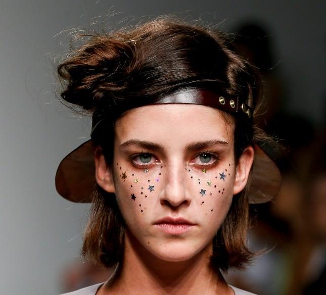 Il particolare capello raccolto è tenuto in ordine da un accessorio street nuovo: la visiera larga portata all'indietro